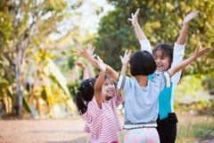 Asiatiska barn lyfter händer och att spela samman med gyckel Royaltyfria Foton