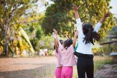 Asiatiska barn lyfter händer och att spela samman med gyckel Royaltyfria Bilder