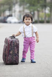 Asiatiska barn som går på gatan med stort resväskabruk för journ Arkivfoto