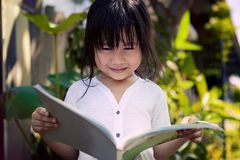 Asiatiska barn som läser en bok i hemträdgård Royaltyfria Foton