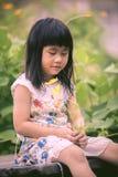 Asiatiska barn som sitter i trädgård med gult kosmos, blommar i mummel Royaltyfri Foto