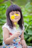 Asiatiska barn som sitter i trädgård med gult kosmos, blommar i mummel Arkivfoton