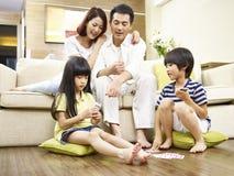 Asiatiska barn som spelar kort medan hålla ögonen på för föräldrar royaltyfri foto