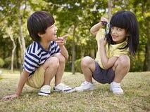 Asiatiska barn som spelar med förstoringsapparaten utomhus Royaltyfri Bild