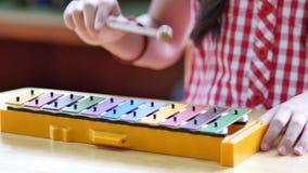 Asiatiska barn som spelar på den färgrika xylofonen arkivfilmer