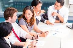Asiatiska Businesspeople som har möte i regeringsställning Arkivfoto