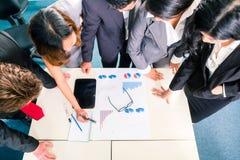 Asiatiska Businesspeople som i regeringsställning möter Arkivfoto