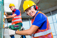Asiatiska byggnadsarbetare som borrar i byggnadsväggar royaltyfri bild