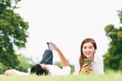 Asiatiska den vänpar eller högskolestudenten som använder mobiltelefonen, lyssnar till musik tillsammans parkerar offentligt, med fotografering för bildbyråer
