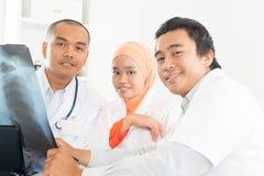 Asiatiska doktorer som diskuterar på röntgenstrålebild fotografering för bildbyråer