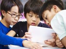 Asiatiska elementära skolpojkar som tillsammans använder minnestavlan Royaltyfria Bilder