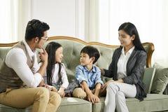 Asiatiska föräldrar och två barn som hemma pratar arkivbilder
