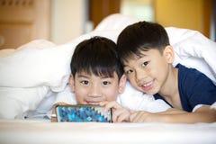 Asiatiska förskole- pojkar som spelar på smartphonen tillsammans Arkivbilder