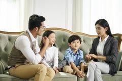 Asiatiska f?r?ldrar och tv? barn som hemma pratar royaltyfria bilder