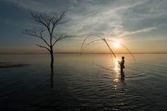 Asiatiska fiskare som fiskar för att fånga sötvattensfisken i natur r Royaltyfri Fotografi