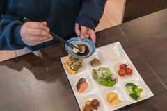 Asiatiska flickabrukspinnar som äter japansk mat royaltyfria foton