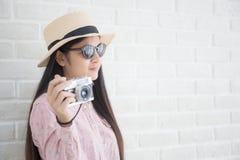 Asiatiska flickaturister använder filmkameran på den vita tegelstenbackgroen fotografering för bildbyråer