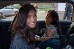 Asiatiska flickor är le och se kameran, medan sitta i bilen royaltyfri bild