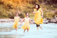 Asiatiska flickor för litet barn som kör och spelar med hennes moder Royaltyfria Bilder