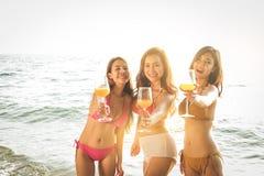 Asiatiska flickor som bär bikinin på stranden arkivbilder