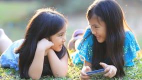 Asiatiska flickor som spelar en lek på den smarta telefonen tillsammans lager videofilmer