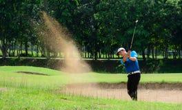 Asiatiska golfare slogg bollen i sanden Hastighet och styrka Arkivbild