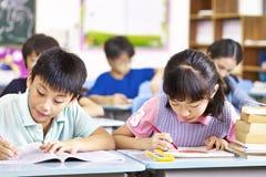 Asiatiska grundskolastudenter i klassrum Fotografering för Bildbyråer