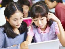Asiatiska grundskolastudenter som arbetar i grupper Arkivbild