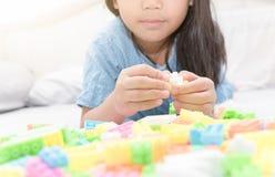 Asiatiska gulliga tegelstenar för flickalekkvarter på säng Royaltyfri Fotografi
