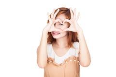 Asiatiska händer för form för flickashowhjärta över henne öga arkivbilder