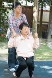 Asiatiska höga kvinnor som spelar gunga på den utomhus- trädgården, parkerar Arkivbilder
