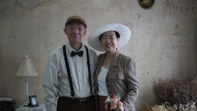 Asiatiska höga par som ler retro stil för klänningtappning i lyx stock video