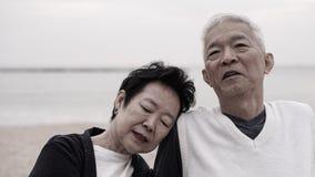 Asiatiska höga par tycker om deras livtid tillsammans på havet Arkivfoto