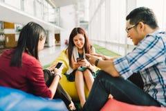 Asiatiska högskolestudenter eller coworkers som tillsammans använder smartphones Rolig modern livsstil, socialt nätverk Arkivbild