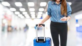 Asiatiska handelsresandekvinnor som söker efter flyg i smartphone på begreppet för lopp för flygplatsterminal royaltyfria foton