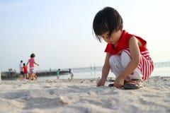 Asiatiska kinesiska barn som spelar sand Arkivbild