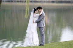 Asiatiska kinesiska par i bröllopsklänning Arkivfoton