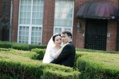 Asiatiska kinesiska par i bröllopsklänning står i buskar Royaltyfria Bilder