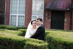 Asiatiska kinesiska par i bröllopsklänning står i buskar Royaltyfri Foto