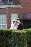 Asiatiska kinesiska par i bröllopsklänning står i buskar Royaltyfri Bild
