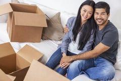 Asiatiska kinesiska par som packar upp askar som flyttar huset Arkivbild