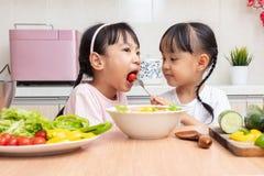 Asiatiska kinesiska små systrar som gör sallad i köket hemmastadd arkivbild