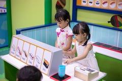 Asiatiska kinesiska små systrar som roll-spelar på sushilagret royaltyfri bild