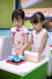 Asiatiska kinesiska små systrar som roll-spelar på sushilagret royaltyfria foton