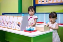 Asiatiska kinesiska små systrar som roll-spelar på sushilagret arkivbilder