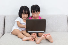Asiatiska kinesiska små systrar som spelar datoren Arkivbilder