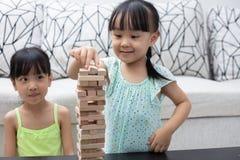 Asiatiska kinesiska små systrar som spelar träbuntar Arkivbilder