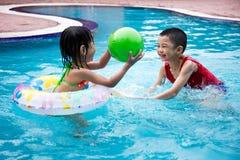 Asiatiska kinesiska små ungar som spelar i simbassängen Royaltyfri Foto