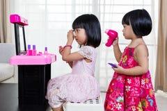 Asiatiska kinesLiitle systrar som spelar med sminkleksaker royaltyfria bilder