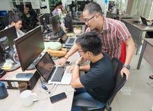 Asiatiska kollegaprogramvarubärare Team Sitting At Desk arkivfoto